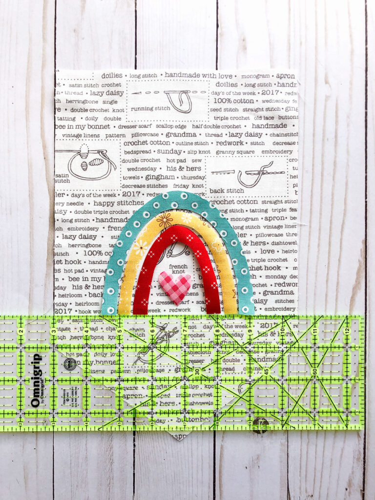 Sew your own colorful rainbow banner from top US sewing blog Ameroonie Designs. Image of positioning applique on front of fabric banner.