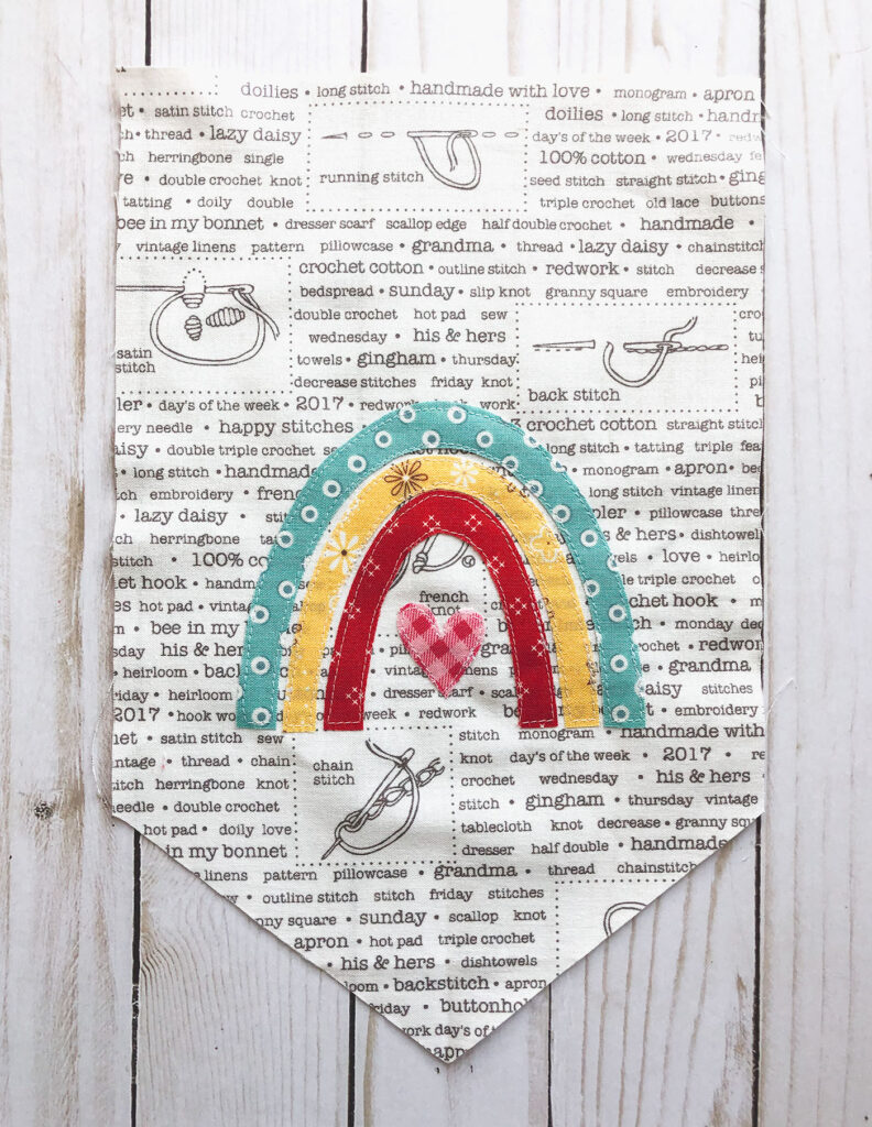 Sew your own colorful rainbow banner from top US sewing blog Ameroonie Designs. Image of applique stitched down on banner.