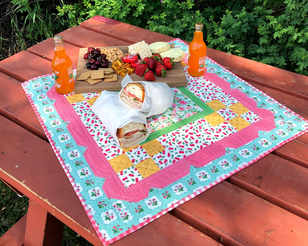 Stunning Scalloped Table Topper by top US sewing blog Ameroonie Designs. Image of table topper on picnic table with charcuterie board and sandwiches.