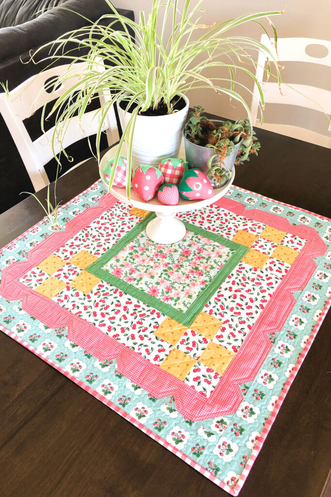 Stunning Scalloped Table Topper by top US sewing blog Ameroonie Designs. Image of table topper on table with cake plate, plants and stuffed fabric strawberries.