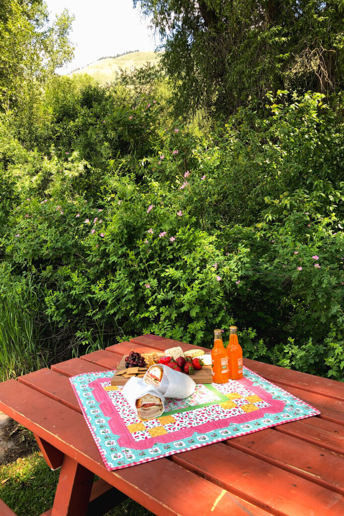 Stunning Scalloped Table Topper by top US sewing blog Ameroonie Designs. Image of table topper with picnic on table with mountain and greenery in background.