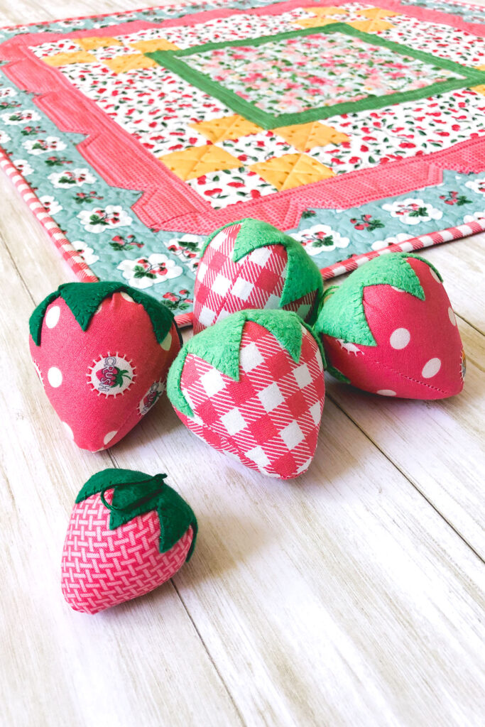 Stunning Scalloped Table Topper by top US sewing blog Ameroonie Designs. Image of fabric strawberries in front of table topper.