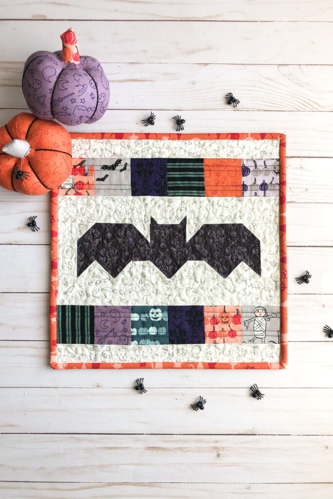 New Halloween Sewing patterns by top US sewing blog Ameroonie Designs. Image of bat mini quilt with fabric pumpkins and plastic spiders.