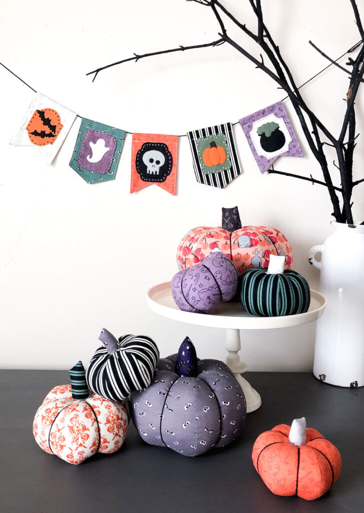 New Halloween Sewing patterns by top US sewing blog Ameroonie Designs. Image of fabric pumpkins in front of black branches with a Halloween banner hanging in the background.