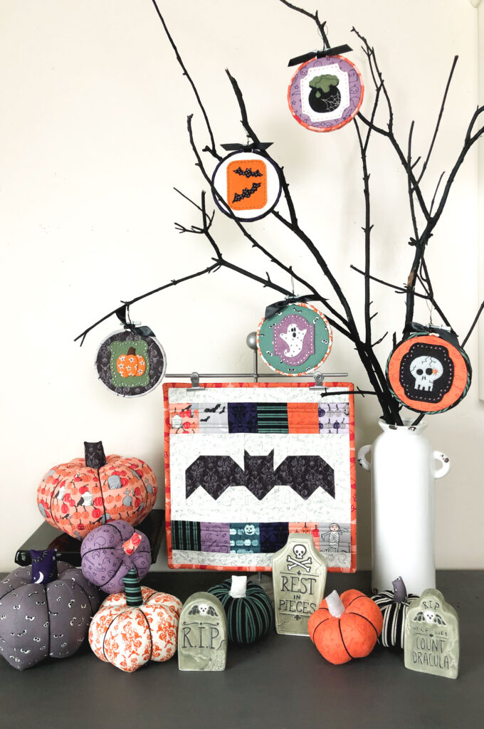New Halloween Sewing patterns by top US sewing blog Ameroonie Designs. Image of black branches with Halloween ornaments and fabric pumpkins plus a mini bat quilt.